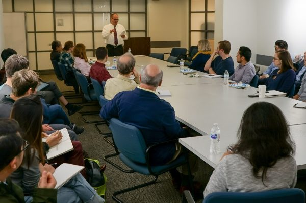 a group of approximately 30 individuals sits around a conference table, looking toward the speaker at the front of the room