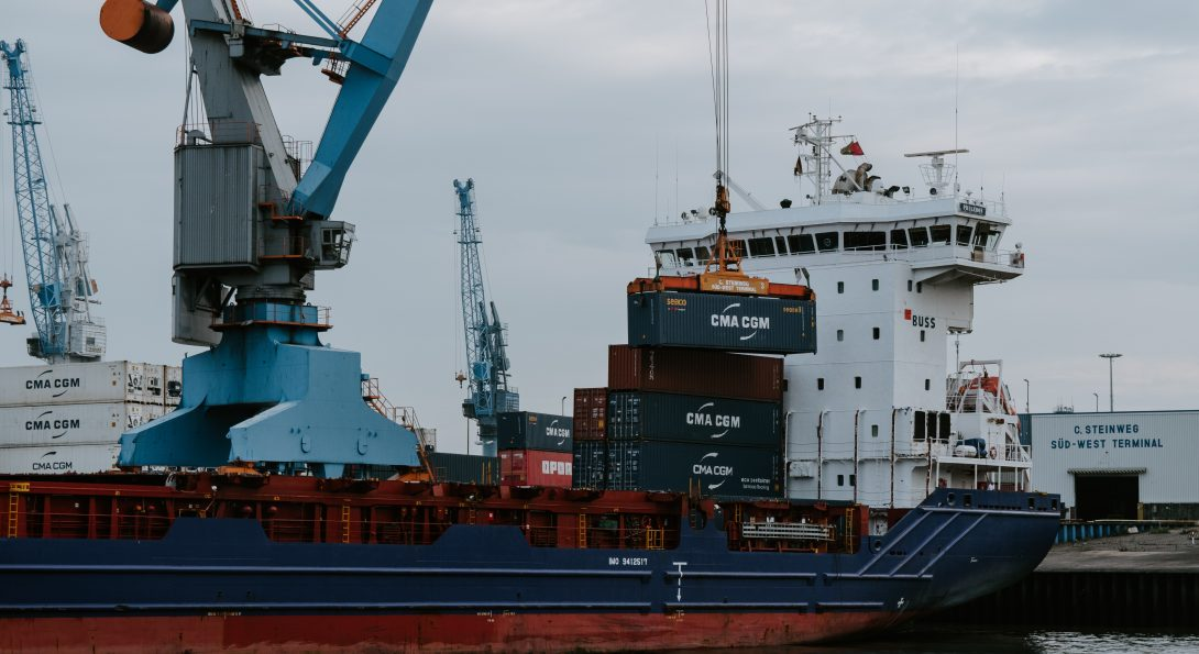 blue and red cargo ship with crane