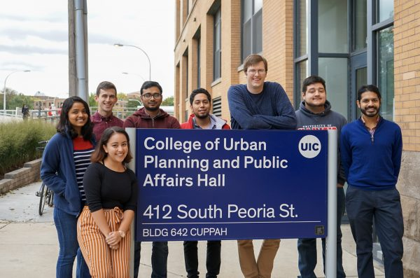 10 people standing around the College of Urban Planning and Public Affairs Hall sign