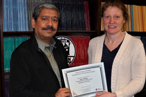 a man and woman stand next to each other in front of a bookcase, holding a certificate between them