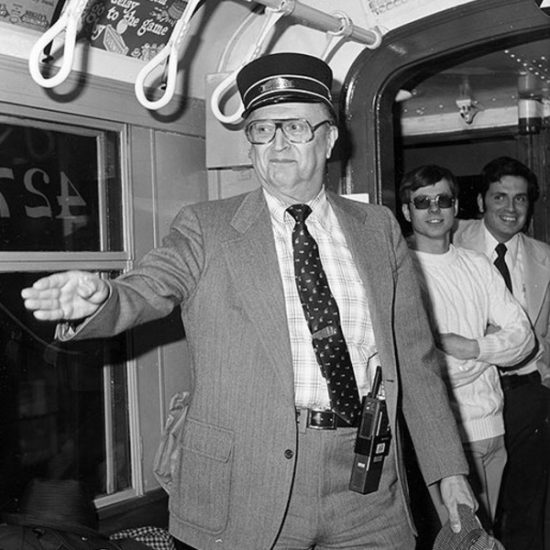 a man stands in a public transit rail car in a black and white photo