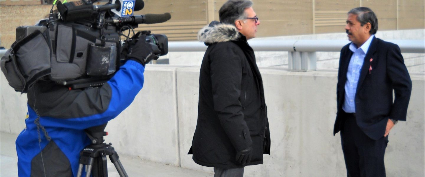a reporter in a heavy winter coat interviews a man wearing a suit. both are standing on a pedestrian overpass; a cameraman stands with a camera on a tripod in the left of the frame