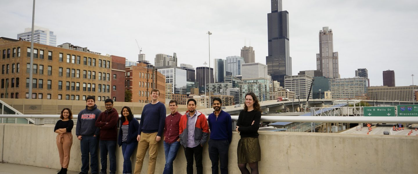 a group of individuals stands on a concrete bridge with the Chicago skyline in the background