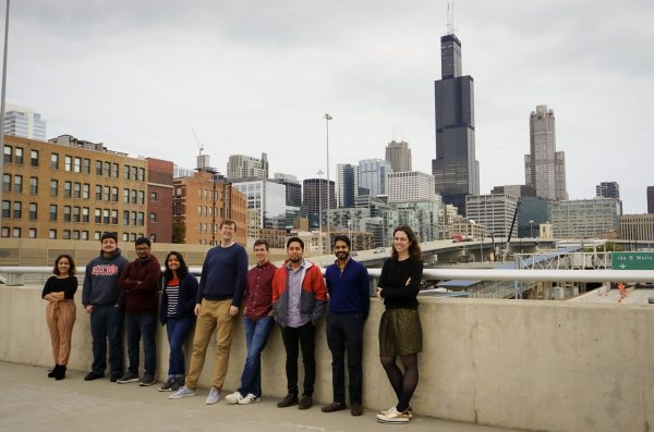 a group of individuals stands on a concrete bridge, the Chicago skyline visible in the background