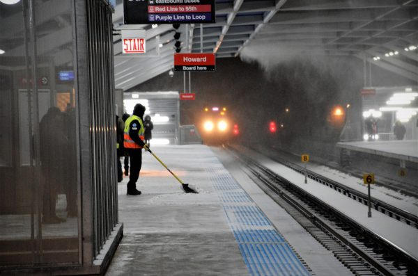 cta train pulls into the station while its snowing