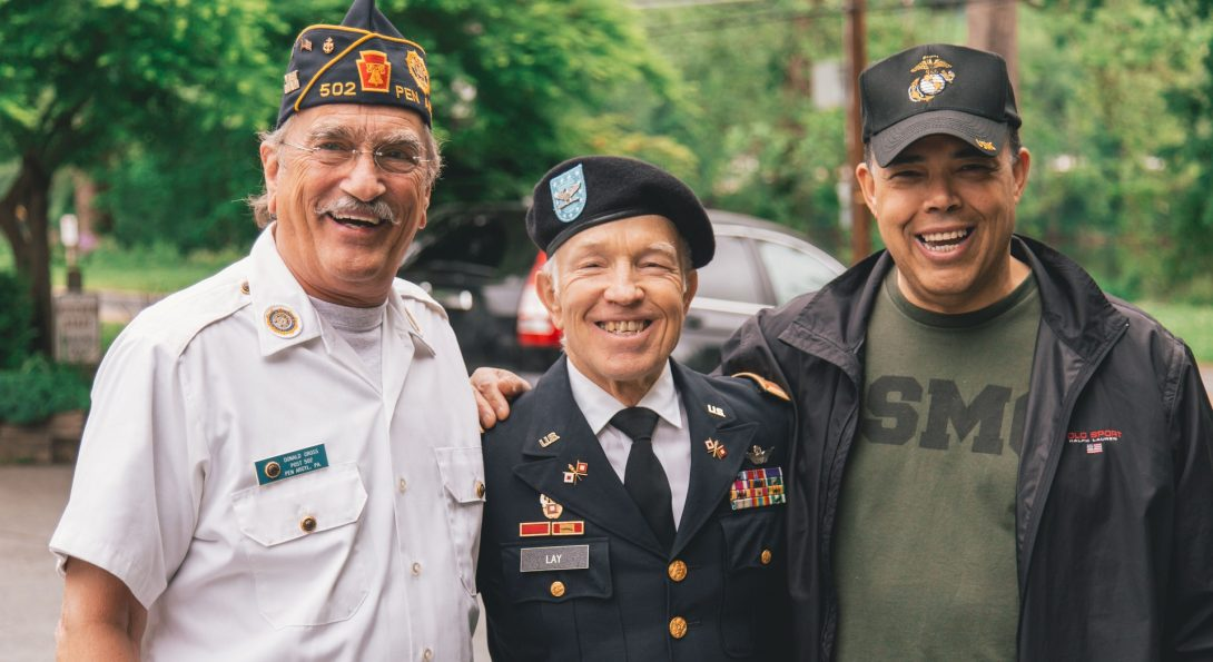 three generations of veterans stand side by side smiling at the camera, trees are visible behind them