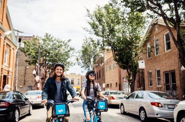 two riders with helmets on Divvy bikes in a Chicago street